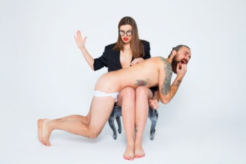 A girl with glasses giving a butt spank to a guy